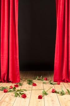 Teatro de palco com cortina vermelha, piso de madeira e rosas