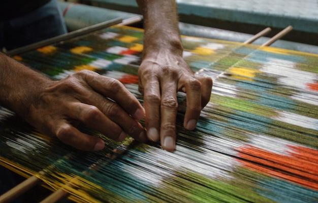 Tecelagem e fabricação de tapetes artesanais closeup. mãos do homem atrás de um tear