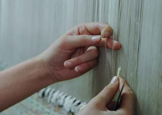 Tecelagem e fabricação de tapetes artesanais closeup. mãos femininas tecem um tapete