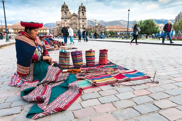 Tecelões nativos não identificados, vestidos com roupas tradicionais, demonstram seu artesanato. cusco.