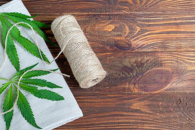 Tecido de cannabis e corda em fundo de madeira. produção industrial.