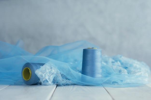 Tecido de cetim azul com fios em um fundo de madeira com miçangas.