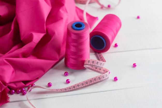 Tecido de cetim rosa com fio e centímetro em fundo de madeira com miçangas.