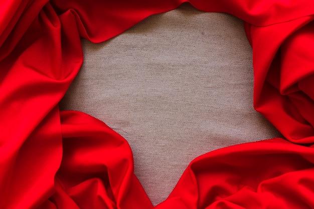 Tecido de cetim vermelho amassado, formando o quadro