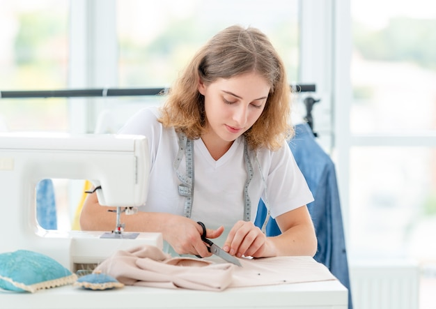 Tecido de corte com costureira com tesoura