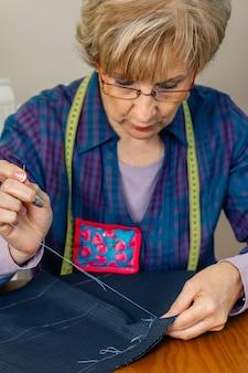 Tecido de costura costureira sênior para fazer uma peça de roupa em sua oficina