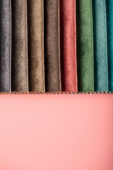 Tecido de couro de alfaiataria de cores marrom e laranja no catálogo na parede rosa