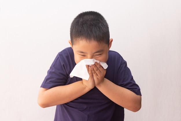 Tecido de doença gripe fria menino asiático soprando coriza