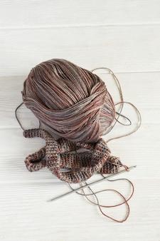 Tecido de malha em tons de inverno cinza, bola de fios e crochê