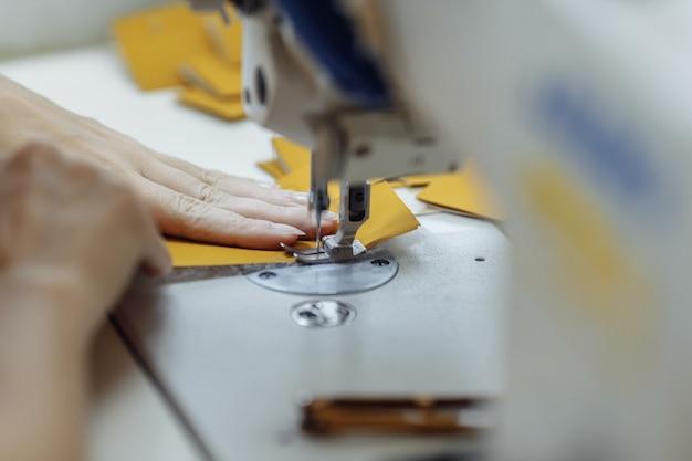 Tecido de rabisco de máquina de costura. alfaiataria na fábrica.