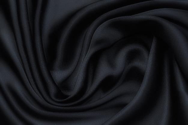 Tecido de seda em preto em layout artístico. textura, plano de fundo, padrão.