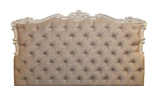 Tecido de veludo macio em tom pastel de cor bege, cabeceira de cama de capitone de sofá estilo chesterfield com moldura de madeira entalhada, isolado no fundo branco, vista frontal