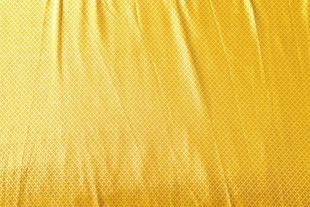 Tecido dourado com estampas em tecido com estampa tailandesa existem alguns vincos. durante o dia, exposto ao sol