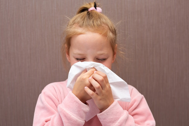 Tecido infantil com gripe resfriada assoando nariz escorrendo