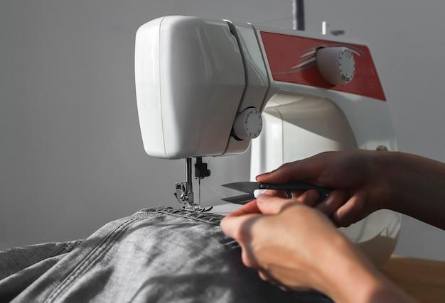 Tecido jeans jeans na máquina de costura fecha as mãos das mulheres no trabalho manual com o cortador