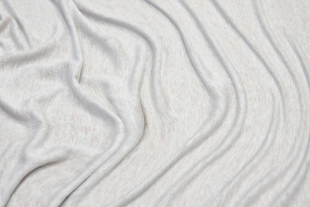 Tecido jersey tecido branco com textura de tecido de fibra de padrões têxteis. esta textura de jersey é elástica e elástica.