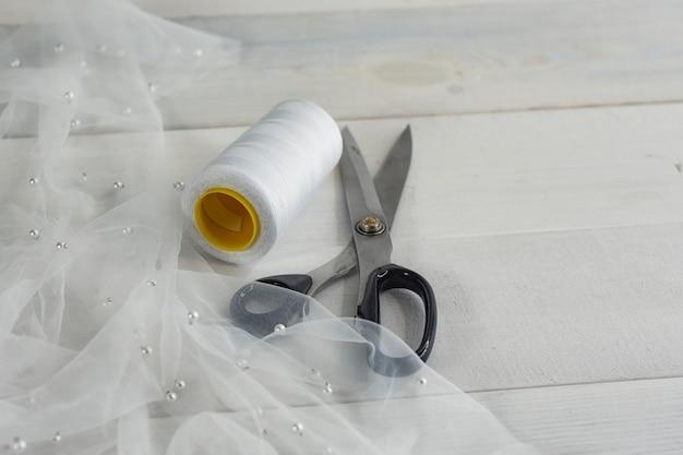 Tecido leve de cetim com fios e tesoura em um fundo de madeira com miçangas.