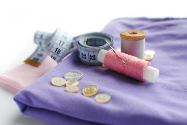 Tecido, linhas de costura, agulha, botões e centímetro de costura.