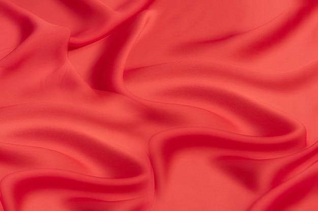 Tecido luxuoso de seda ou viscose vermelha. plano de fundo e padrão.