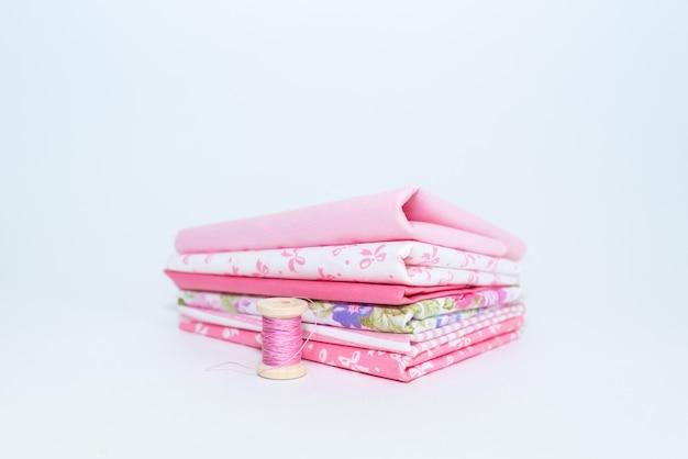 Tecido natural rosa e ferramentas de costura na mesa de madeira branca