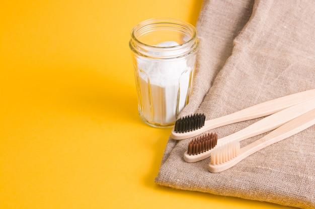 Tecido natural, várias escovas de bambu diferentes e um frasco de refrigerante em uma superfície amarela