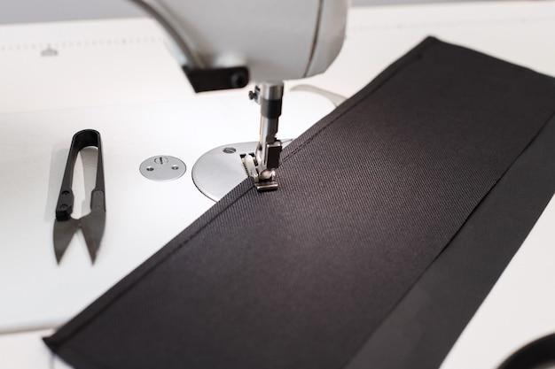 Tecido perto da máquina de costura na mesa da costureira. fechar-se