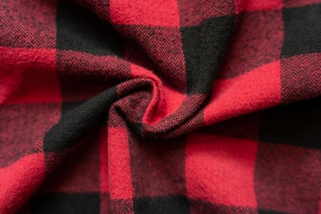Tecido preto e vermelho amassado em uma gaiola