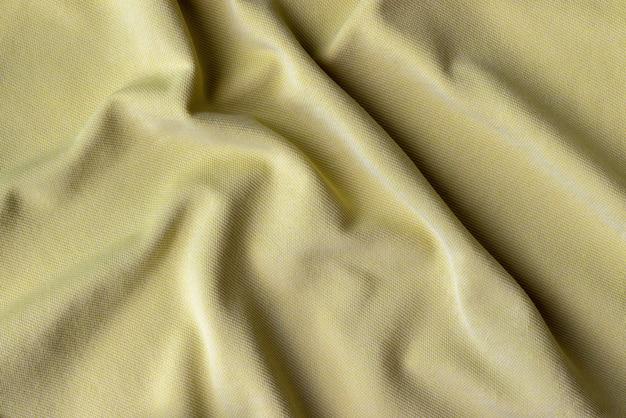 Tecido tecido de malha de algodão. fundo amarelo de tecido amarrotado
