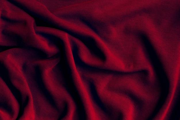 Tecido tecido de malha de algodão. fundo de tecido vermelho escuro amarrotado