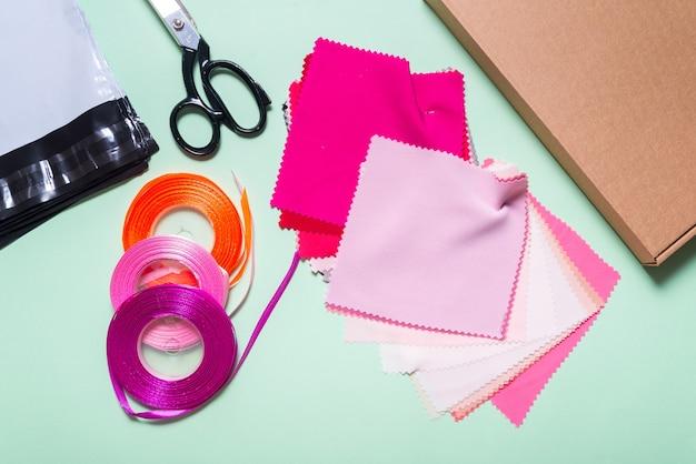 Tecido têxtil e fita na mesa de trabalho da costureira