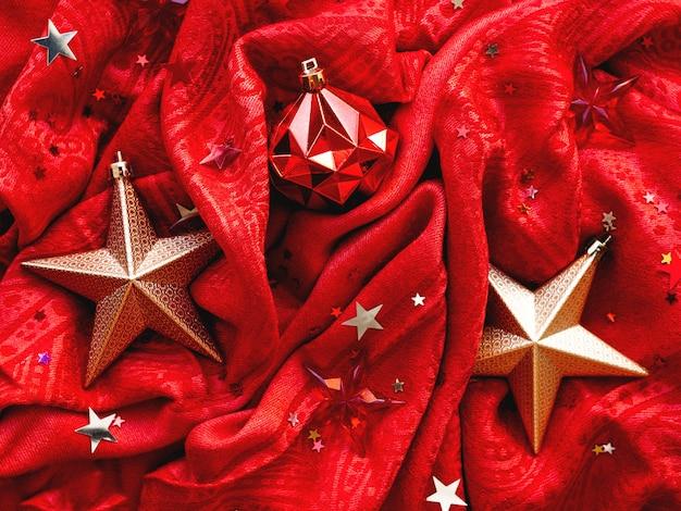Tecido vermelho brilhante com estrelas douradas e bola