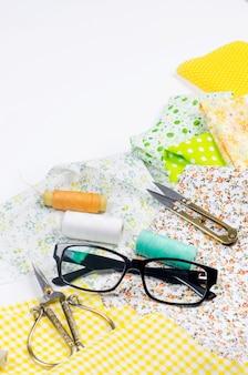 Tecidos amarelos e verdes coloridos, tesouras, botões, carretéis de linha e óculos em branco.
