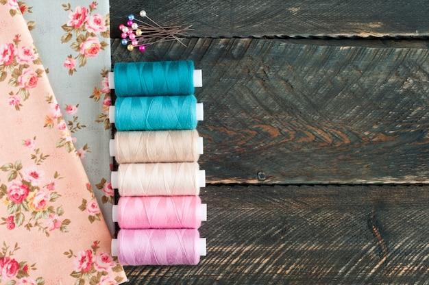 Tecidos, carretéis de linha e pinos no fundo de madeira velho. acessórios de costura