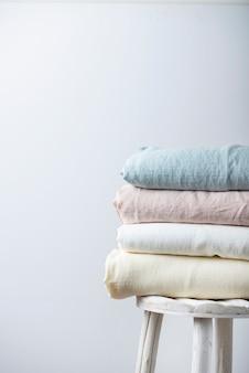Tecidos de linho natural em tons pastel no fundo claro. conceito de costura