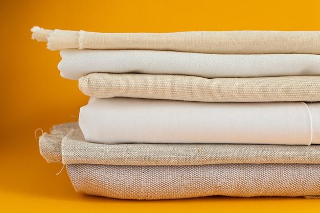 Tecidos naturais de cor marfim - linho e algodão estão empilhados em uma pilha sobre uma superfície amarela.