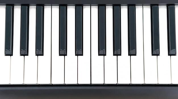 Tecla de piano closeup na mesa de madeira com foco seletivo, teclado de sintetizador midi eletrônico para estúdio em casa criativo