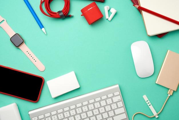Teclado, banco de potência dourada com cabo, smartphone vermelho com tela preta em branco