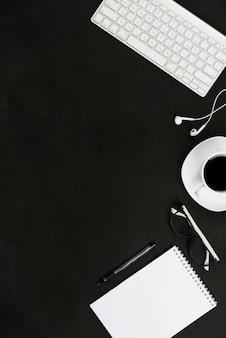Teclado branco; fone de ouvido; xícara de café; óculos; bloco de notas caneta e espiral contra a mesa preta