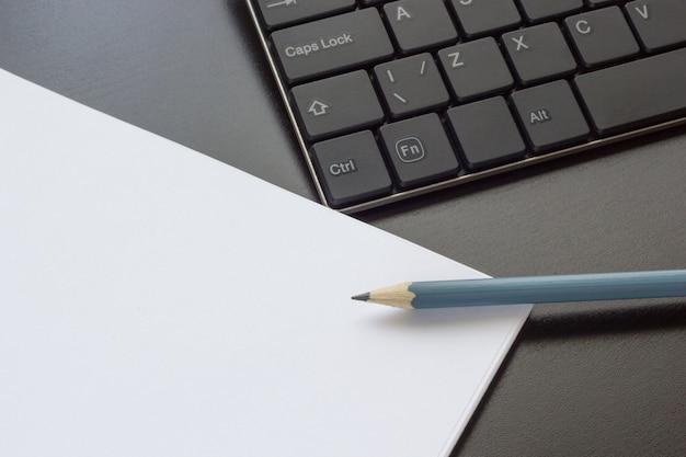 Teclado, caderno e lápis sobre a mesa, vista superior