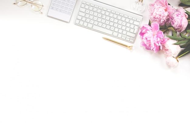 Teclado, caneta dourada, óculos, calculadora e um buquê de peônias rosa em um fundo branco. copie o espaço.