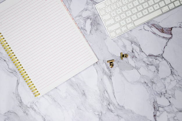 Teclado, clipes e caderno
