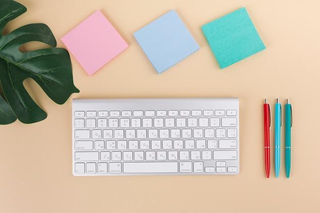 Teclado com adesivos e canetas na mesa