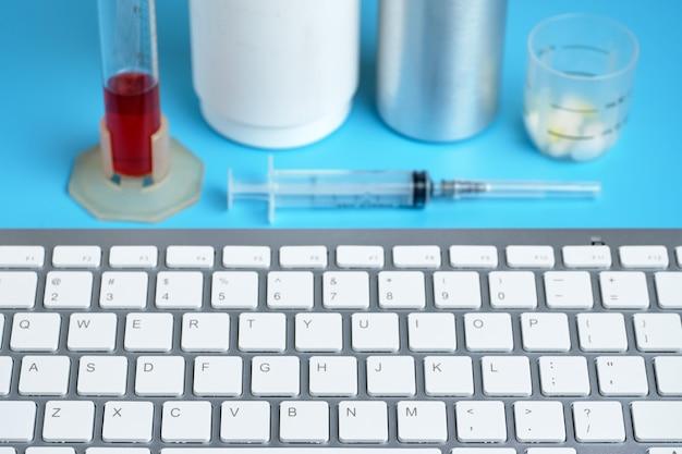 Teclado com diferentes equipamentos médicos, sobre um fundo azul.