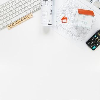 Teclado com modelo de casa e blueprint na mesa de escritório de imóveis