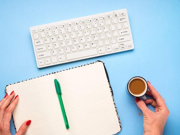 Teclado com notebook aberto e xícara de café