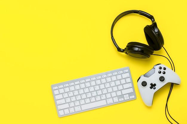 Teclado, controlador e fones de ouvido em um fundo amarelo. o conceito do console do jogo. vista plana leiga, superior.