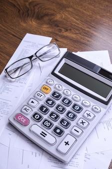 Teclado da calculadora com cheques da loja de compras em um piso de madeira