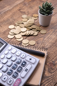 Teclado da calculadora, moedas de ouro, caneta e caderno em um fundo de piso de madeira
