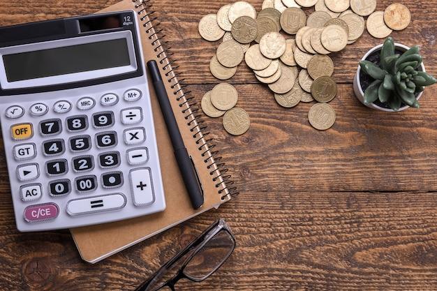 Teclado da calculadora, moedas de ouro, caneta e caderno em um piso de madeira
