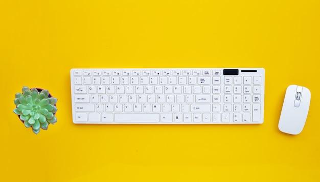 Teclado de computador branco e mouse com cacto na superfície amarela